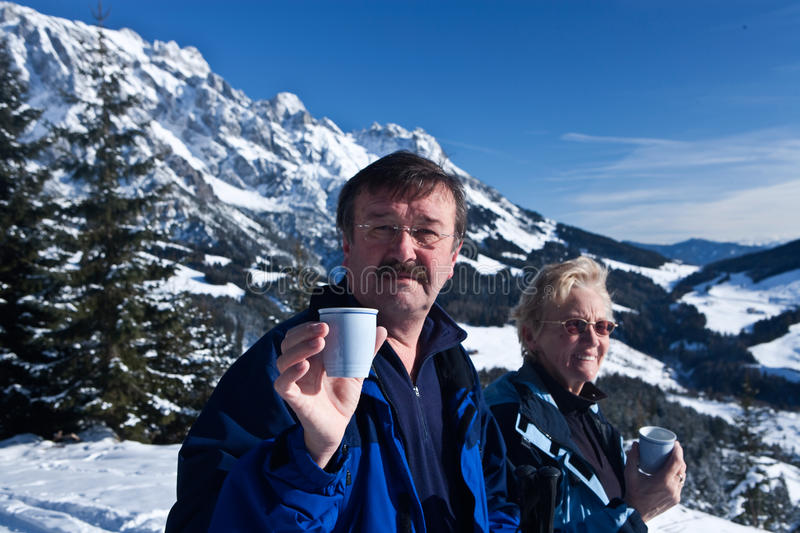 Alpine seniors. A senior couple in a winter setting in the alpine mountains. Active and happy seniors.They are having a cup of tea stock image