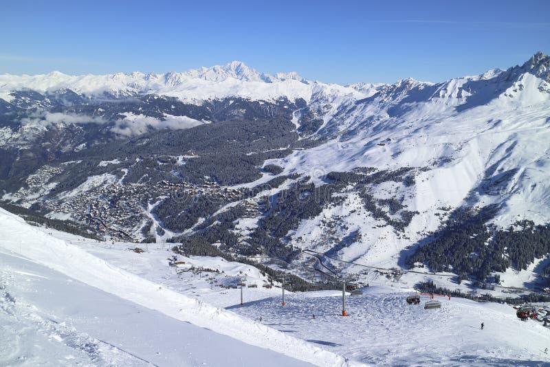 Alpine ski resort valley against snowy mountain range royalty free stock photography