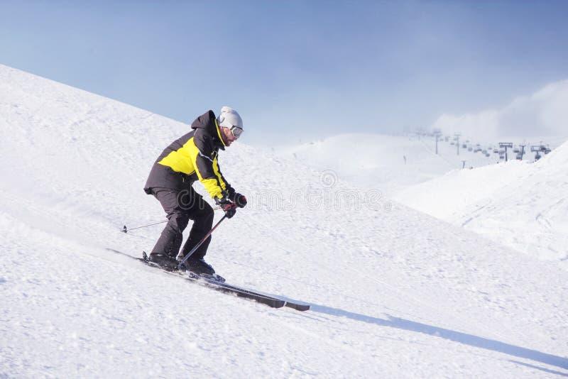 Alpine skier on piste running downhill stock images