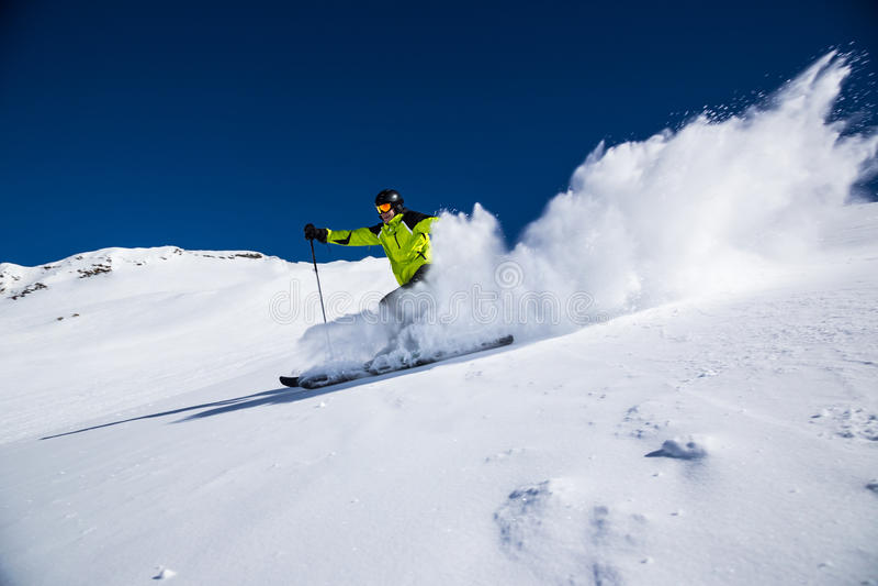 Alpine skier on piste, skiing downhill royalty free stock photo