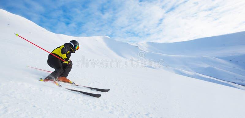 Alpine skier skiing in mountains stock photos