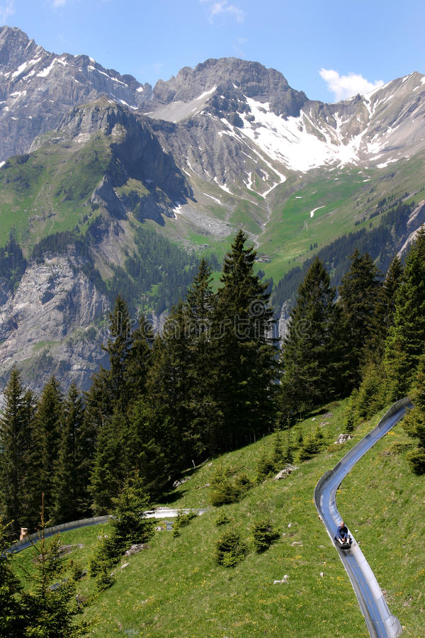 Alpine Slide in the Swiss Alps. An alpine slide winds its way down the mountain, high in the Swiss Alps stock photos
