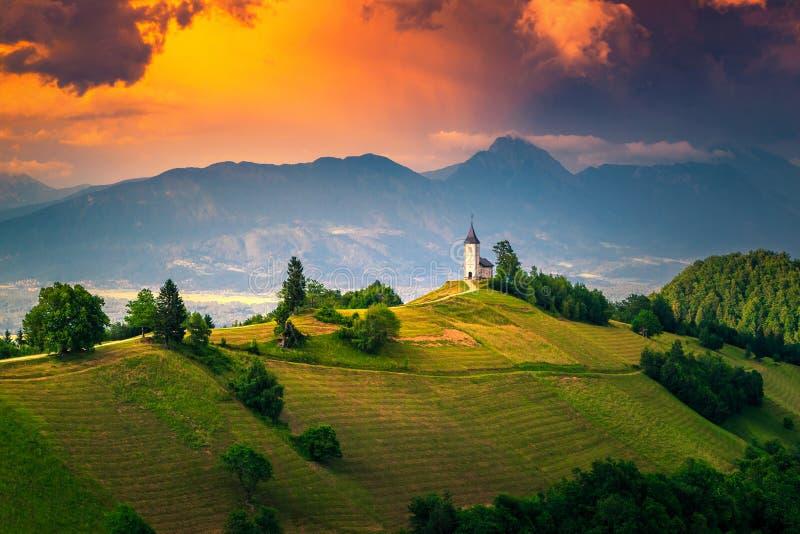 Alpine Sonnenunterganglandschaft mit Heiliges Primoz-Kirche, nahe Jamnik, Slowenien lizenzfreie stockfotografie