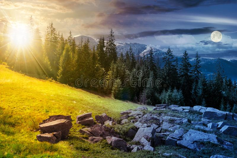 Alpine summer landscape day and night time change composite. Rock formation near the spruce forest on a grassy hill. mountain with snowy top in the distance royalty free illustration