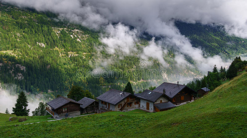 Alpine village in foggy clouds royalty free stock photo