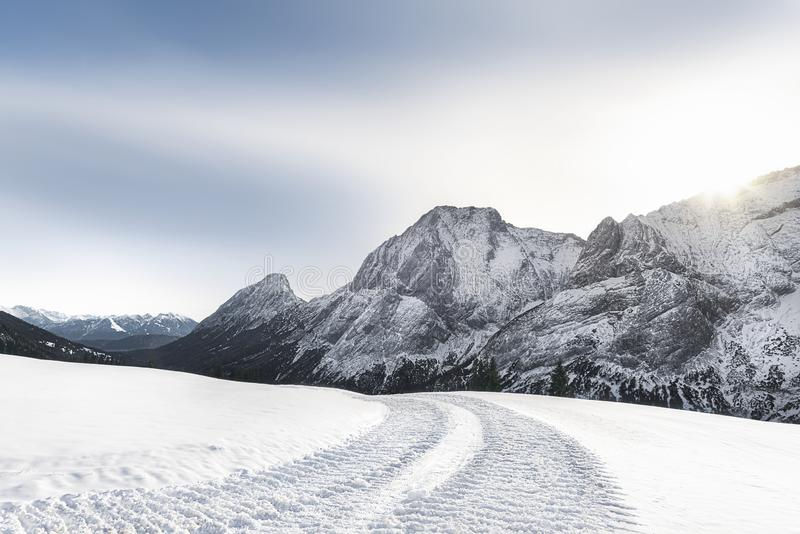 Alpine winter landscape with snowy mountains and snowy road royalty free stock photos