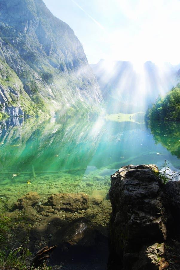 Alpiner See mit Sonnestrahlen stockfotografie