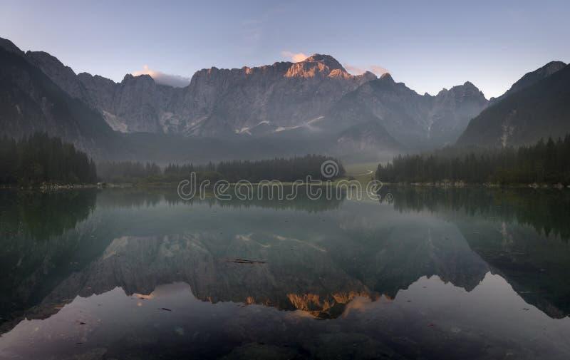 Alpiner See, Sonnenaufgang über dem alpinen See Laghi di Fusine lizenzfreie stockfotografie