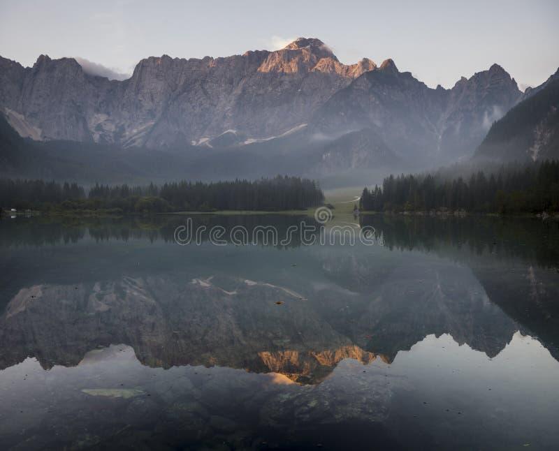 Alpiner See, Sonnenaufgang über dem alpinen See Laghi di Fusine lizenzfreies stockbild
