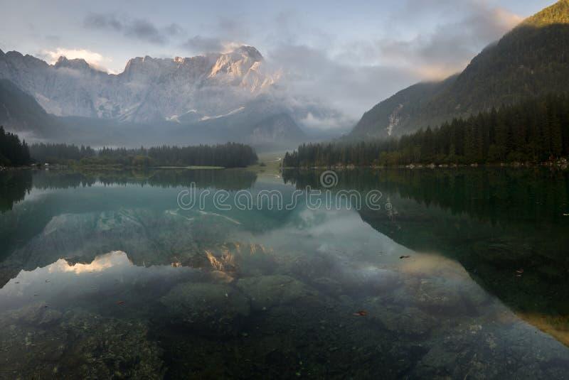 Alpiner See, Sonnenaufgang über dem alpinen See Laghi di Fusine lizenzfreie stockbilder