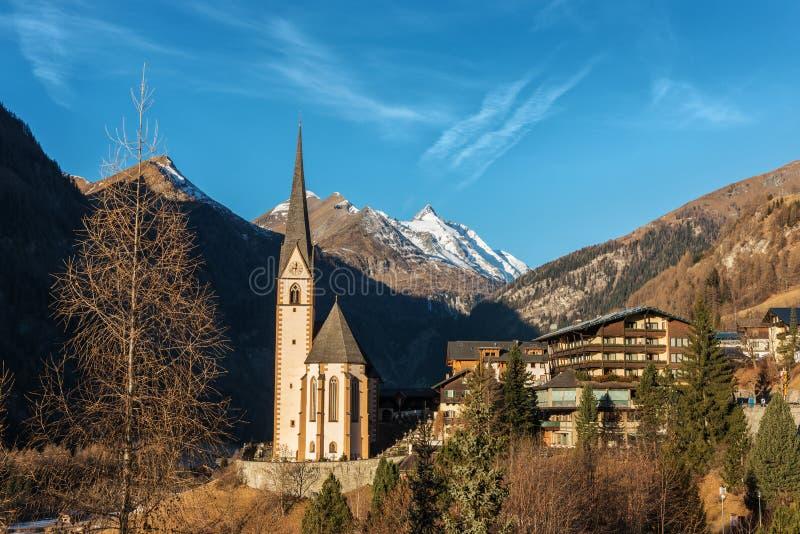 Alpines Dorf mit schöner Pilgerfahrtkirche und blauem Himmel stockbilder