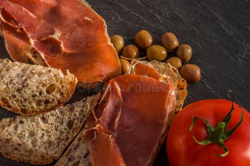 Alpines Stangenbrot mit jamon, Oliven und Tomate auf Schwarzem stockfotos