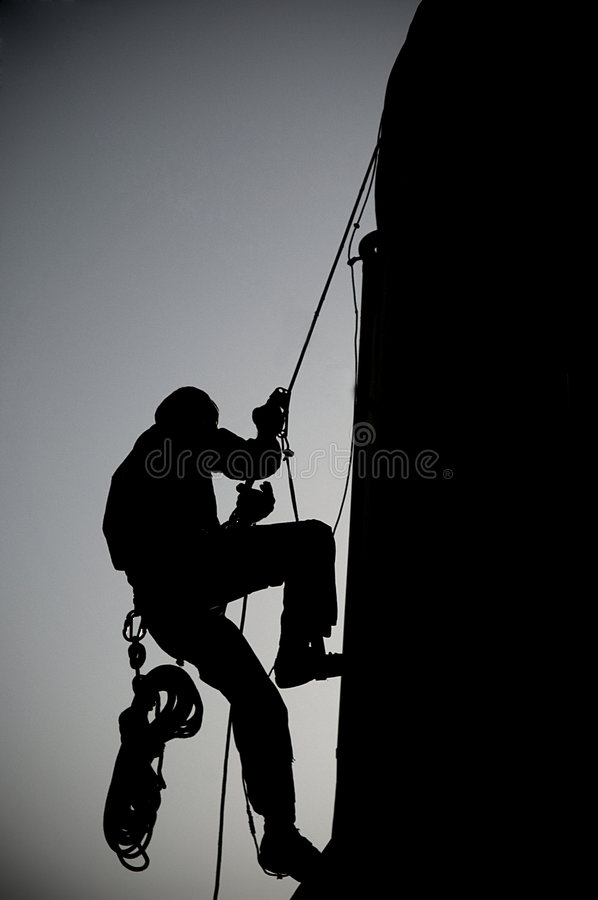 Alpinist. Silhouette photo of alpinist working stock image