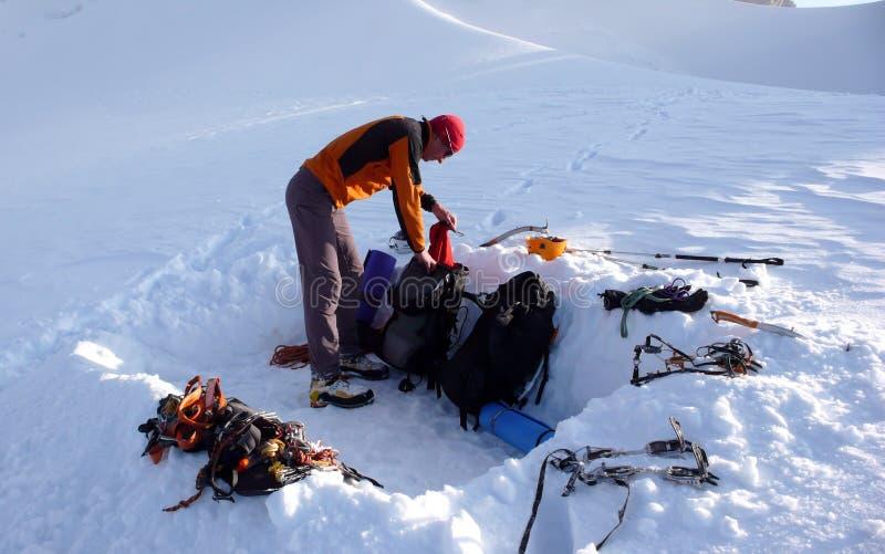 Alpinist die klaar voor een koude bivy nacht in een snowhole op een gletsjer in de Alpen worden stock fotografie