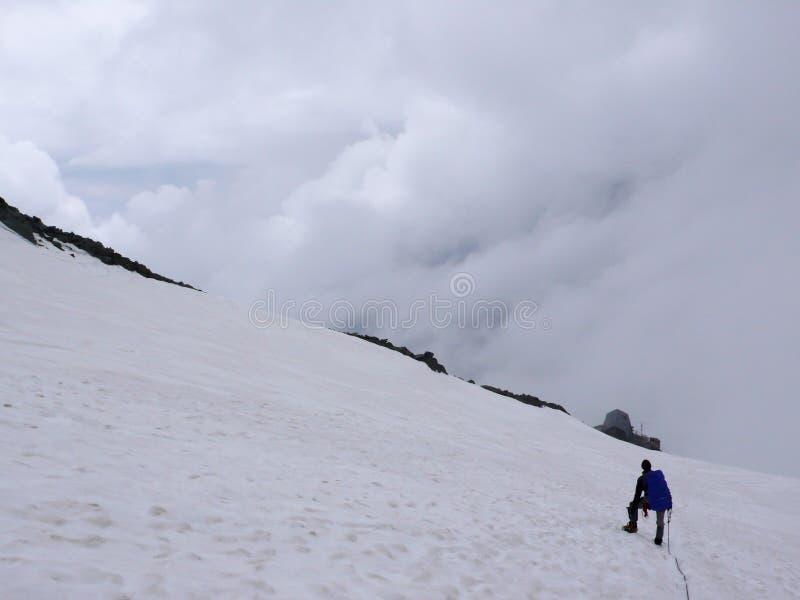 Alpinist die onderaan over een alpiene gletsjer met een berghut wandelen in gezicht royalty-vrije stock foto