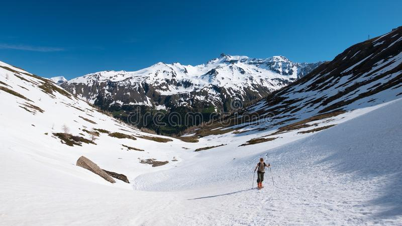 Alpinist hiking ski touring on snowy slope towards the mountain summit. Concept of conquering adversities and reaching the goal. Alpinist hiking ski touring on stock image