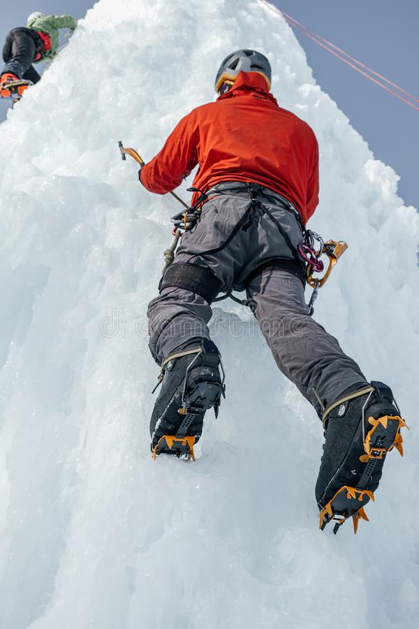 Alpinist man with ice tools axe climbing a large wall of ice. Ou. Tdoor Sports Portrait royalty free stock image