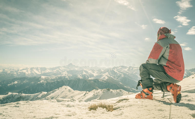 Alpinist on the mountain top. Alpinist kneeling on the mountain summit. Shot in backlight, stunning panoramic view of the alpine arc. Concept of success and royalty free stock photo