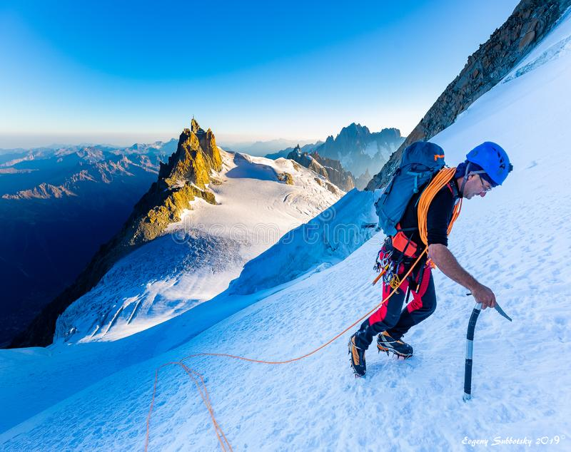 Alpinist mountaineer climbing snow ice mountain slope. Alpinist guy mountaineer man climbing ascending Mont Blanc du Tacul snow mountain slope. Aiguille du Midi stock photos