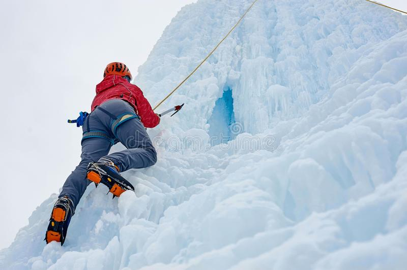 Alpinist woman with ice tools axe in orange helmet climbing a l. Arge wall of ice. Outdoor Sports Portrait royalty free stock photos