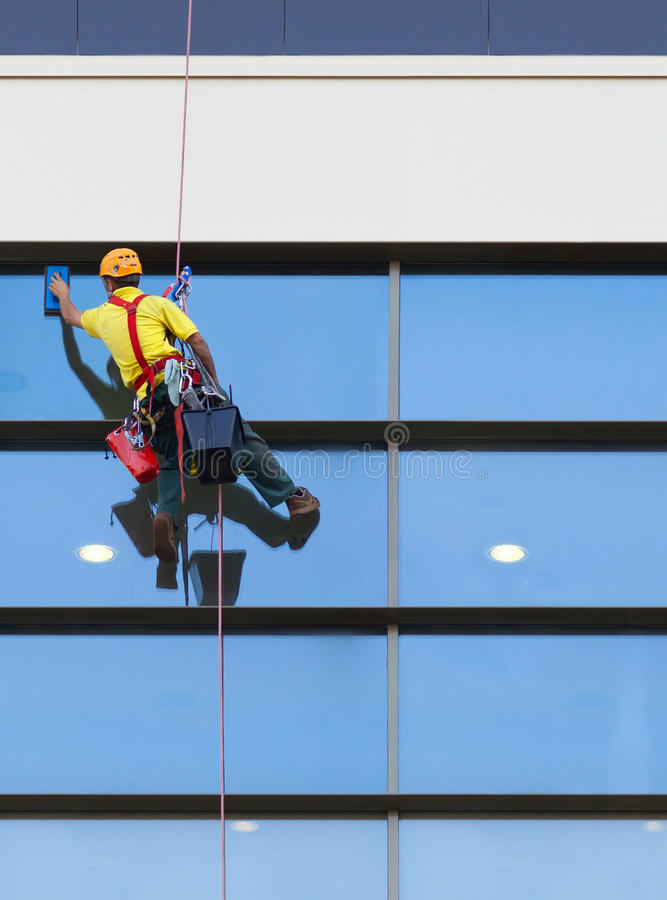 Alpinist worker washing windows of the modern building.  royalty free stock images