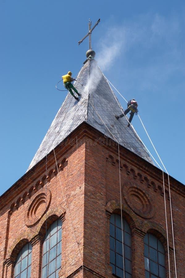 Alpinist zwei säubert Kirchedach stockfotografie