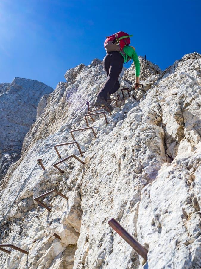 Alpinista che scala il verticale appena sotto la cima della montagna immagini stock libere da diritti
