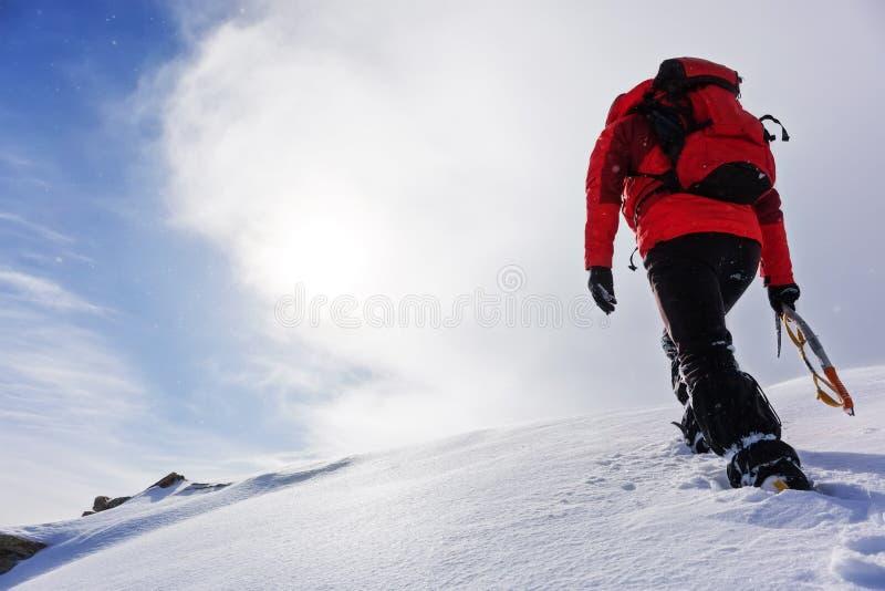 Alpinista che scala un picco nevoso nella stagione invernale fotografia stock libera da diritti
