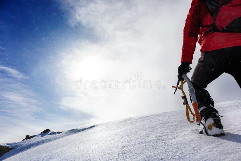 Alpinista che scala un picco nevoso nella stagione invernale fotografia stock