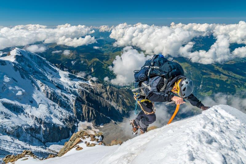 Alpinista extremo na alta altitude na cimeira da montanha de Aiguille de Bionnassay, maciço de Mont Blanc, cumes, França imagens de stock royalty free