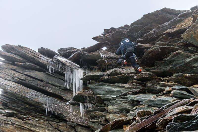 Alpinista na seção, no risco e no perigo rochosos congelados extremamente perigosos nas montanhas altas, cumes, França imagem de stock