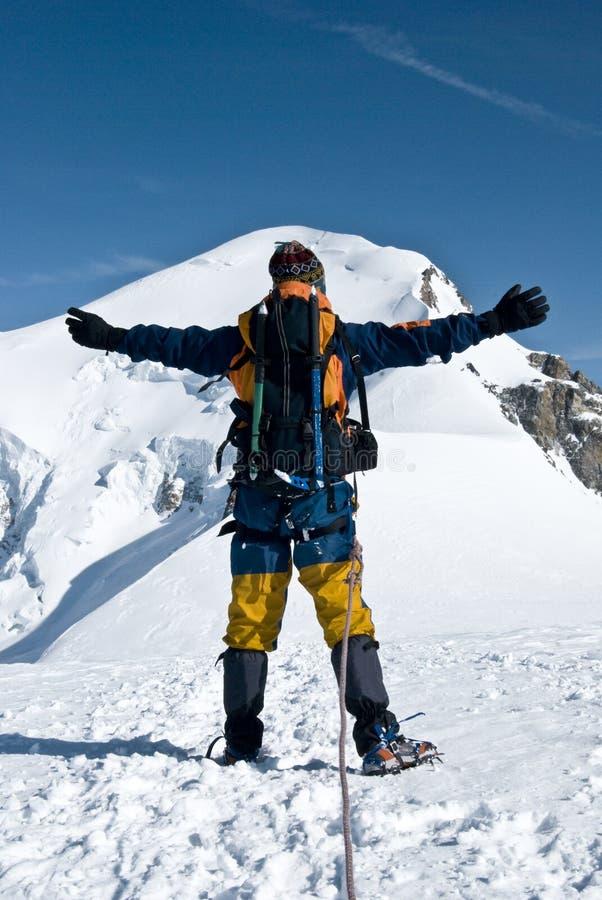 Alpinista que abraça o pico fotos de stock