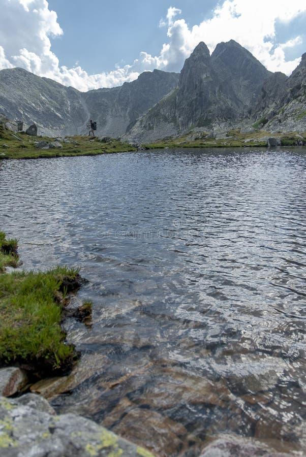 Alpinista sylwetki plakat jeziorem z wysokimi szczytami fotografia royalty free