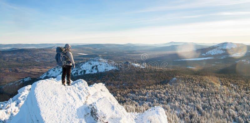 Alpinista wspinał się halnego wierzchołek, mężczyzna wycieczkowicza pozycję i śnieg, przy szczytem zakrywającym z lodem skała, wi fotografia stock