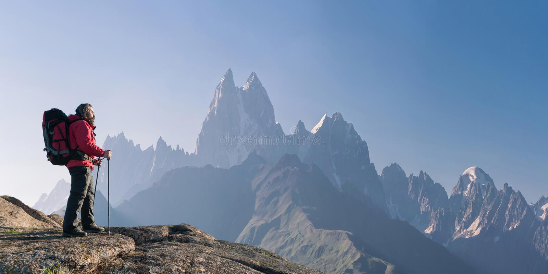 Alpinista z plecakiem na skale zdjęcie stock