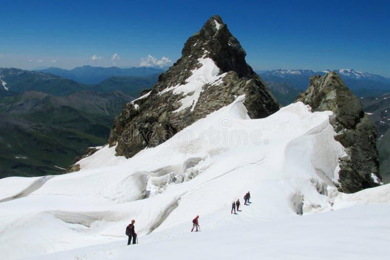 Alpinistas na neve e nas rochas foto de stock