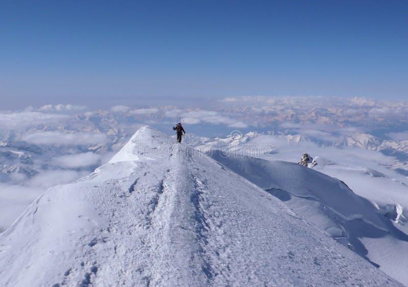 Alpiniste masculin de ski d'arrière-pays trimardant le long d'un étroit et d'une arête exposée de sommet d'une crête alpine élevé photos libres de droits