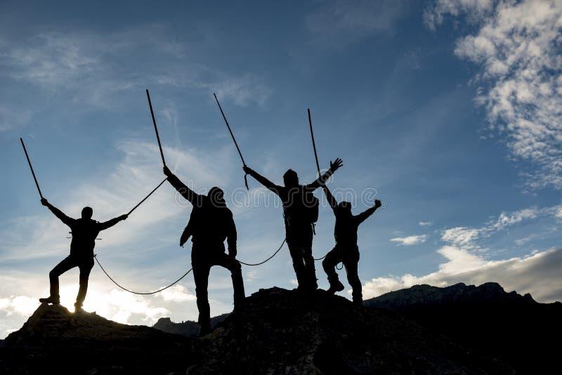 Alpinistes silhouettés sur le sommet photographie stock