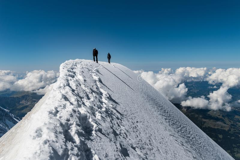 Alpinists on Aiguille de Bionnassay summit - extremely narrow snow ridge above clouds, Mont Blanc massif, France. Extreme alpinists on Aiguille de Bionnassay royalty free stock images
