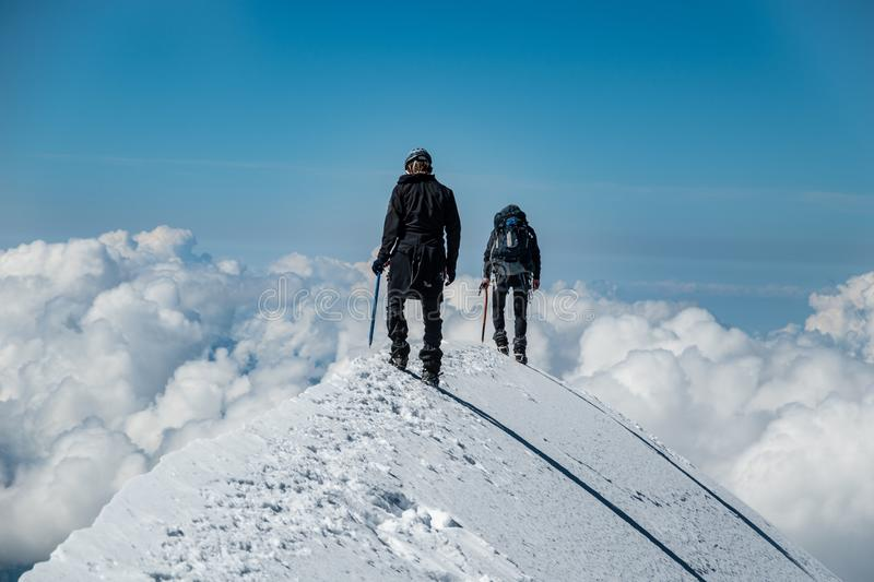 Alpinists on Aiguille de Bionnassay summit - extremely narrow snow ridge above clouds, Mont Blanc massif, France. Two alpinists on Aiguille de Bionnassay summit stock image