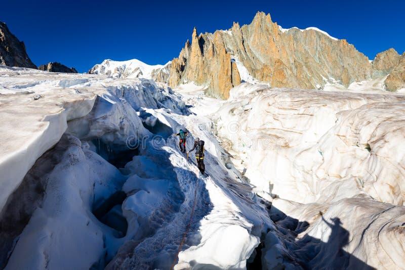 Alpinists crossing glacier crevasse, Aiguilles du Diable peak, Mont Blanc. Alpinists people crossing climbing glacier crevasse ice crack, Aiguilles du Diable royalty free stock image