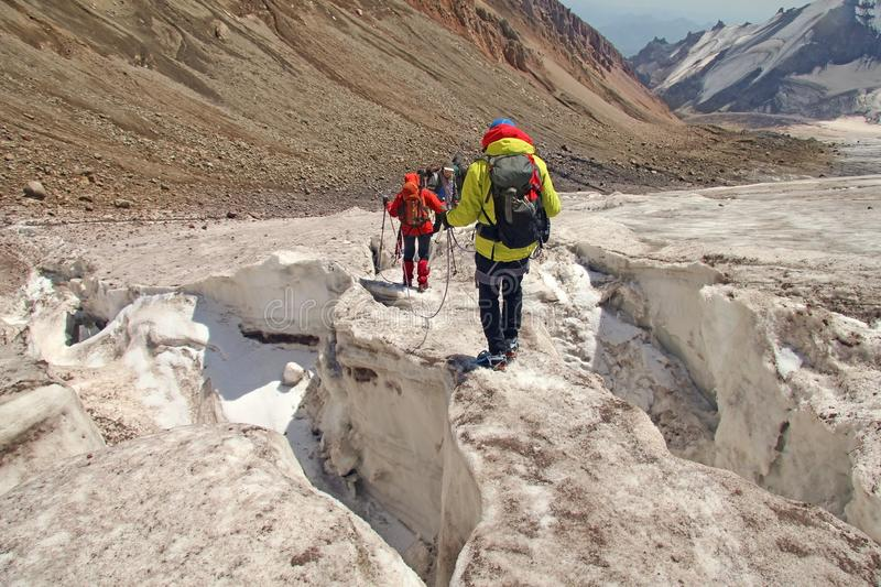 Alpinists mountaineers climbing over ice snow crevasse crack. Extreme sport mountain climbing of Mount Kazbek one of the major mountains of the Caucasus on the stock images