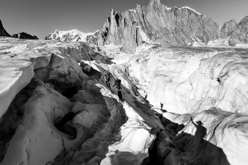 Alpinists crossing glacier crevasse, Aiguilles du Diable peak, Mont Blanc. Alpinists people crossing climbing glacier crevasse ice crack, Aiguilles du Diable stock photo