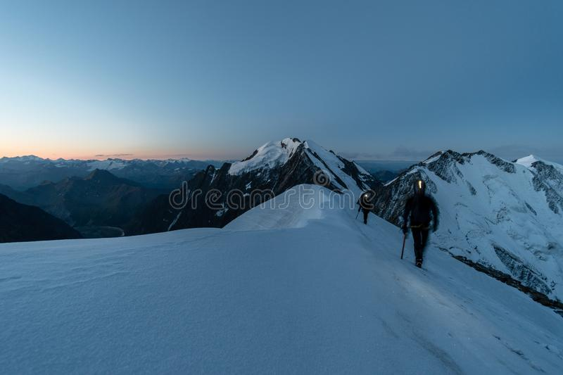 Alpinists on snowy ridge early before sunrise, Aiguille de Bionnassay, Mont Blanc massif, France. Extreme alpinists on snowy ridge early before sunrise, Aiguille stock image