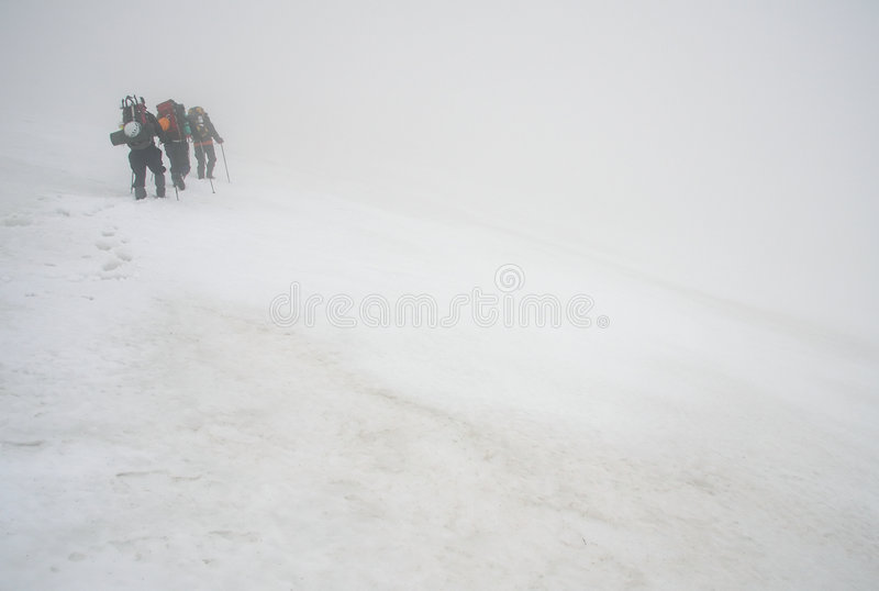 Alpinists and stormy weather stock images