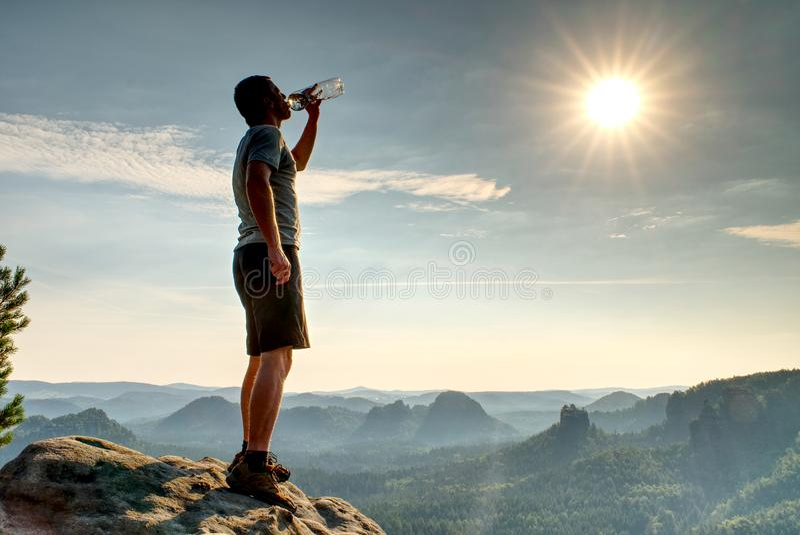 Alpinisty napój od plastikowej kolby przy mglistych gór tłem fotografia stock