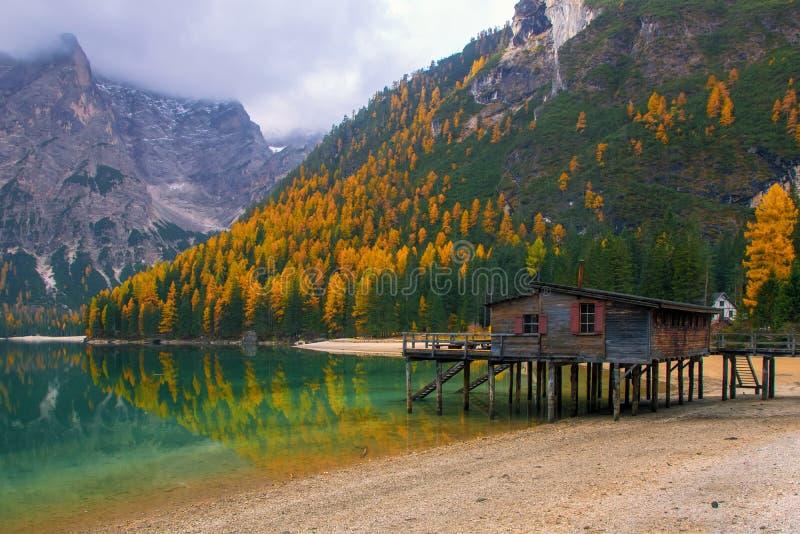 Alpint landskap för härlig höst, spektakulärt gammalt träskeppsdockahus med pir på Braies sjön, Dolomites, Italien royaltyfria foton