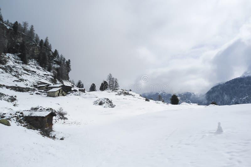 Alpint landskap med den gamla skjul och lite snögubben royaltyfria bilder