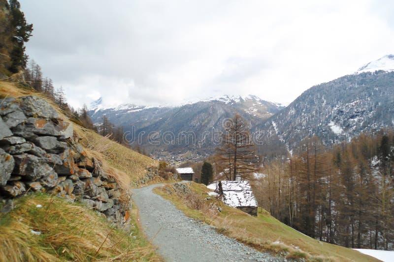 Alpint landskap med grusvägen längs berglutningen royaltyfri foto