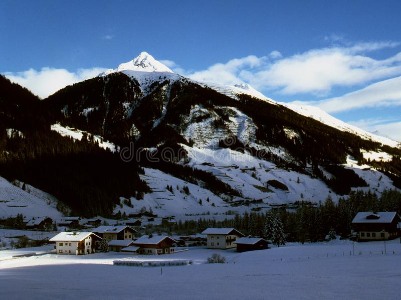 view of the alpine village on the background of mountain peaks stock image